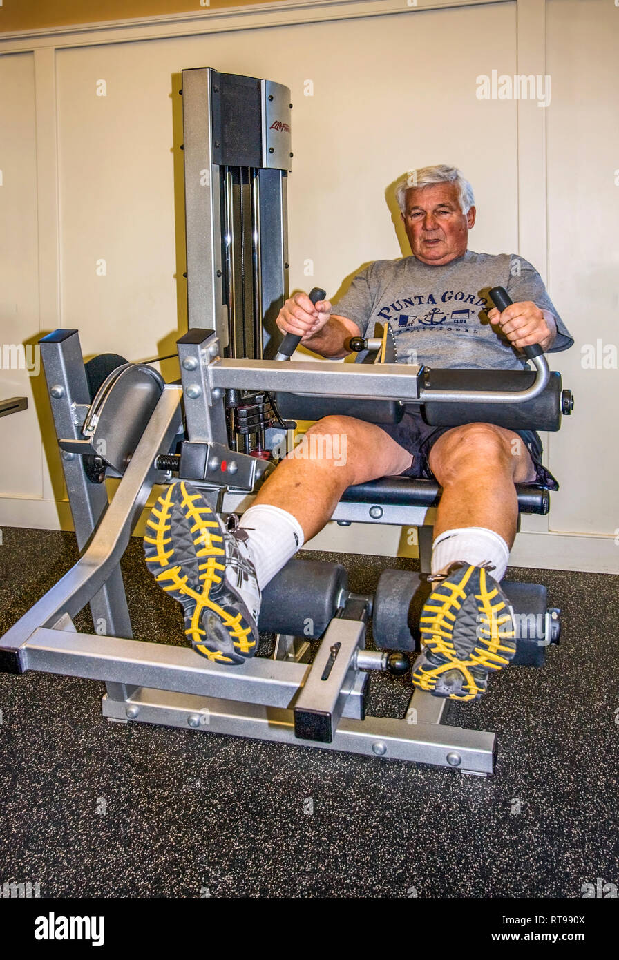 senior man exercising; fitness machine; health center; healthy; conditioning; effort, strengthening, physical activity, work out, vertical; MR - Stock Image