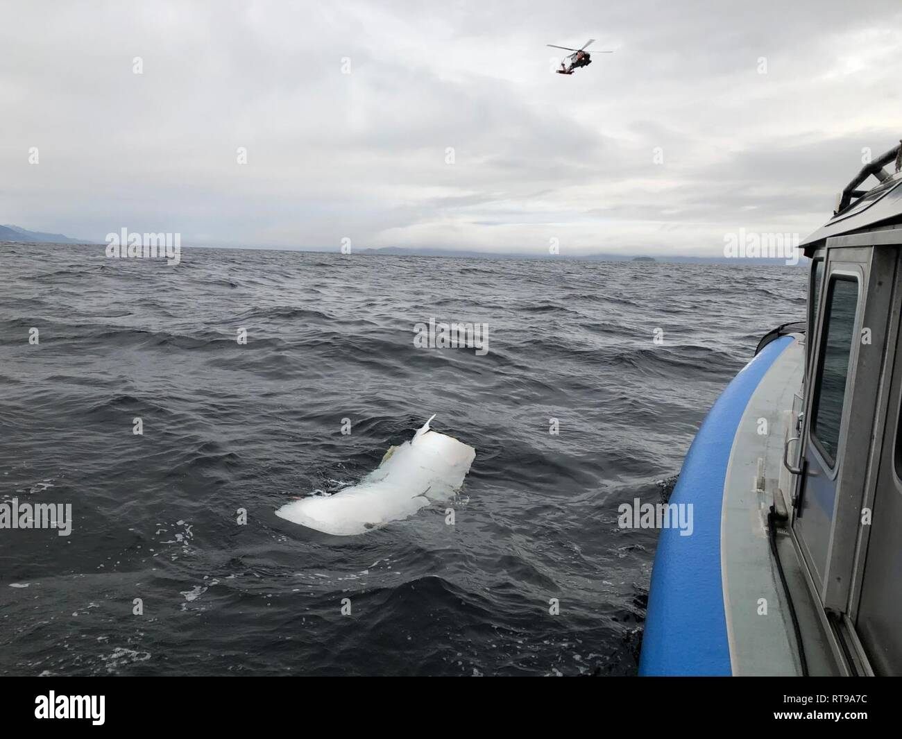 A Coast Guard Air Station Sitka MH-60 Jayhawk helicopter crew flies over a piece of debris spotted by Alaska Wildlife Troopers while searching for three people aboard an overdue Guardian Life Flight aircraft 20-miles west of Kake, Alaska, Jan. 30, 2019. Coast Guard Cutters Anacapa and Bailey Barco, along with an Alaska Army National Guard, several search and rescue teams and good Samaritans began searching for the aircraft and three people aboard after it did not arrive as scheduled to Kake Jan. 29, 2019, to retrieve a patient for transport. - Stock Image
