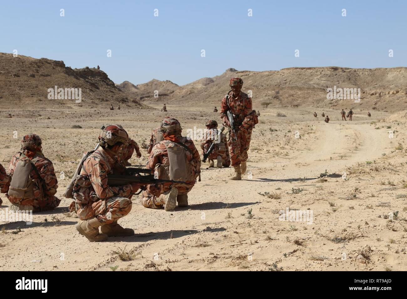 An Omani squad leader checks the status of his Soldiers