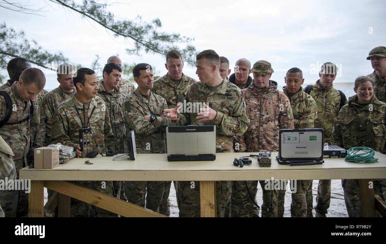 Service members from the Joint Communications Support Element and the British Army's 30th Signal Regiment gather around U.S. Army Staff Sgt. Kevin Shells (center), a JCSE systems team chief, at Beer Can Island, Fla. Jan. 30, 2019, as he demonstrates how to set up and utilize communications equipment in a deployed environment with no power source. As part of the Cobb Ring exercise, the two nations trained together to demonstrate capabilities with coalition partners and strengthen relationships. Stock Photo