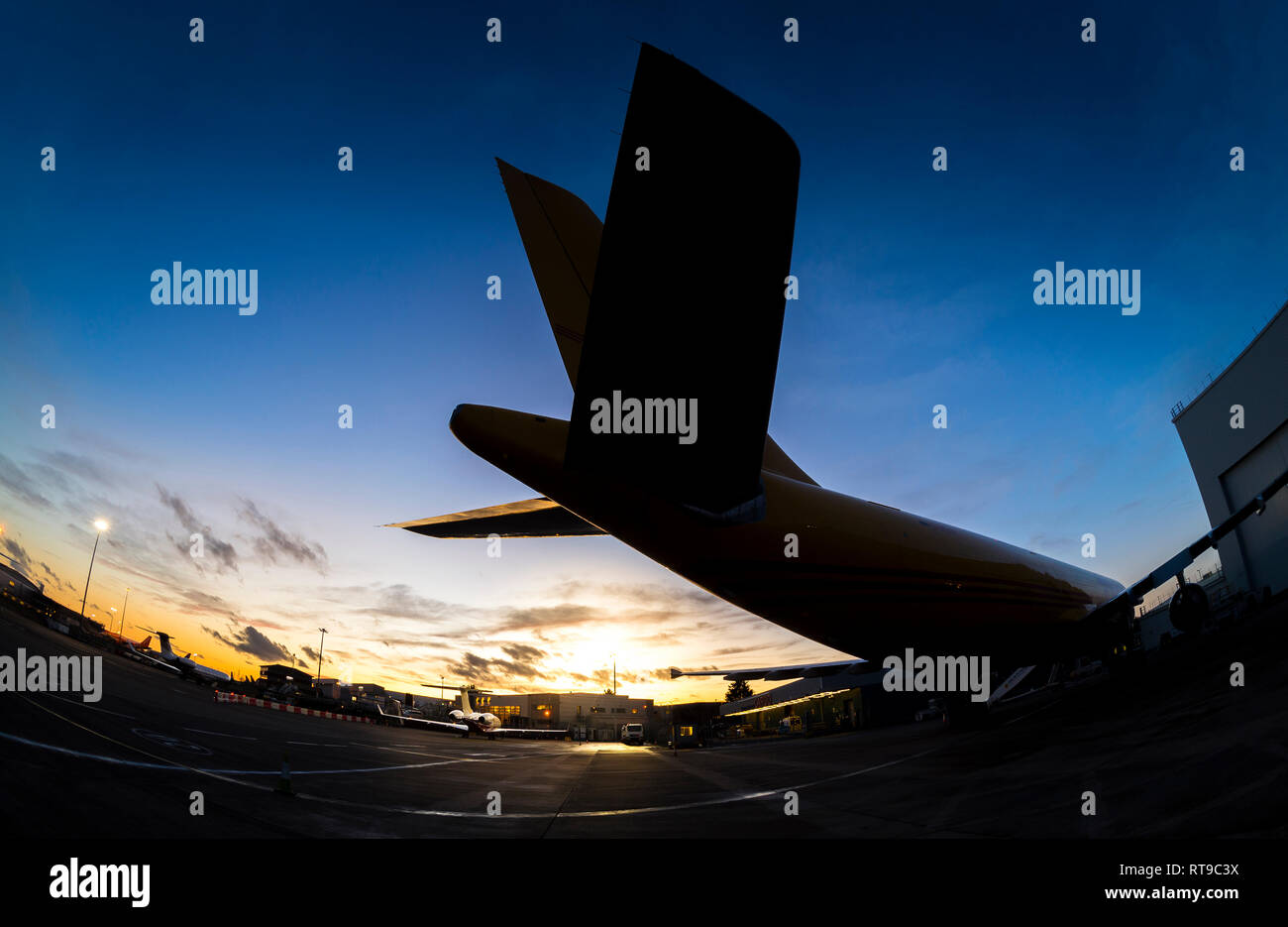 Silhouette of the tail fins of an aeroplane at Luton airport at dusk. - Stock Image
