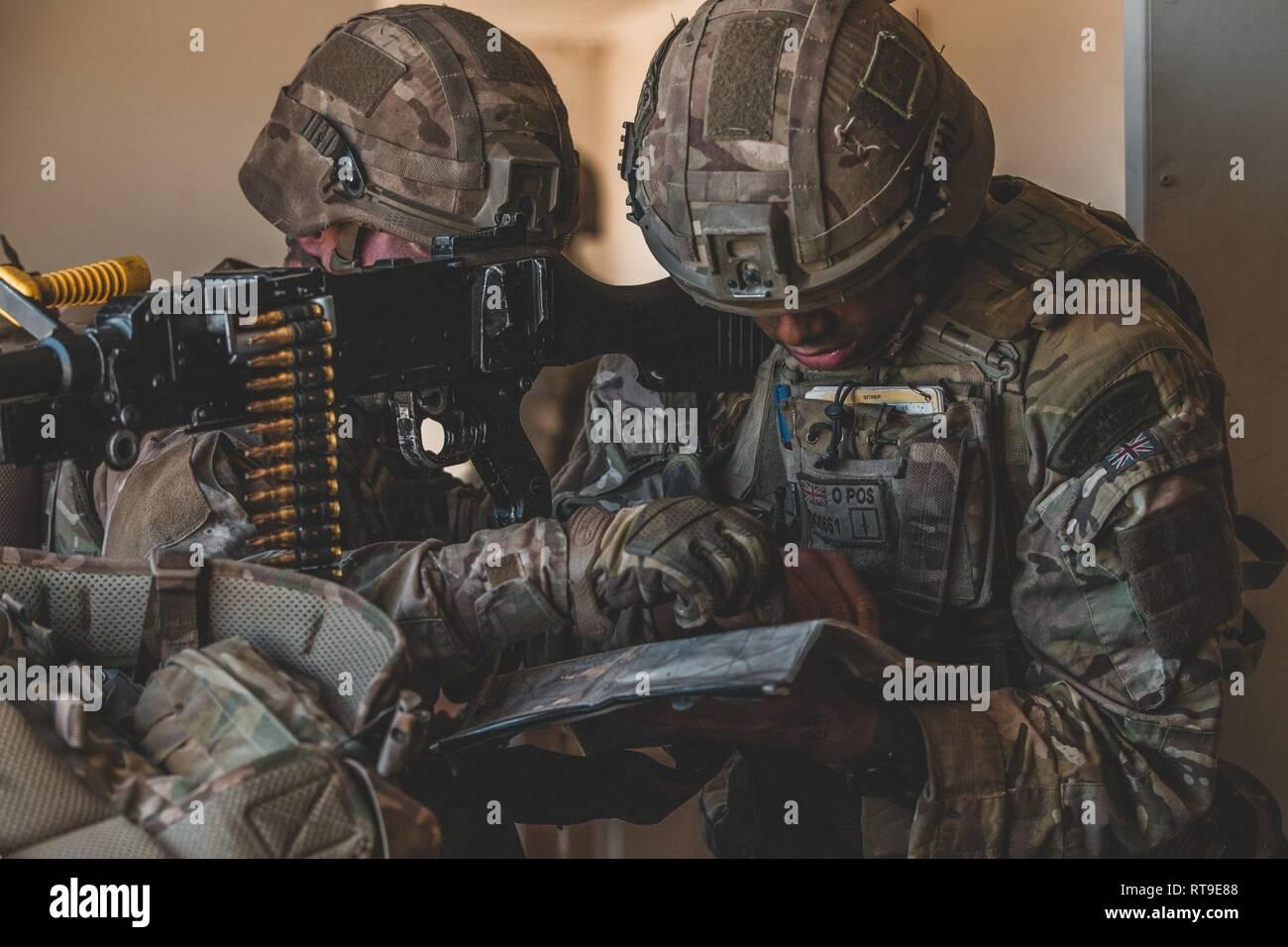 U K  Royal Marines with 45 Commando analyzes a map of Range