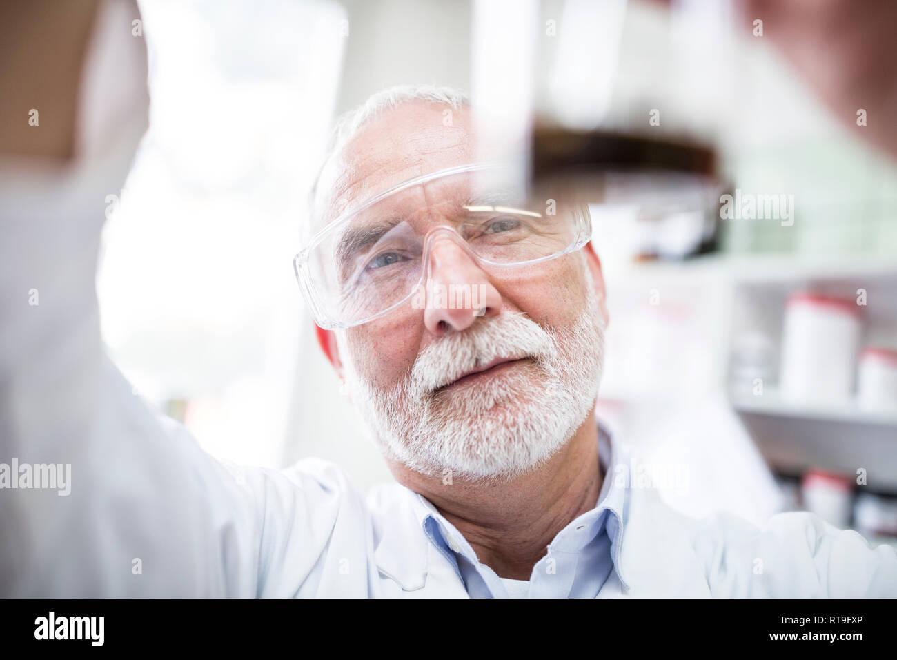 Man looking at beaker in laboratory - Stock Image