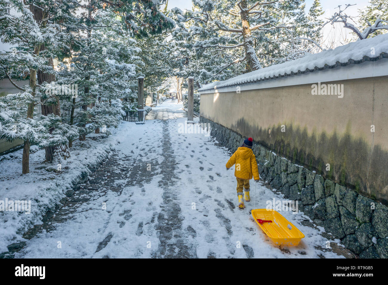 2017 kid playing with a plastic sledge in old Kyoto street in winter time. - Stock Image