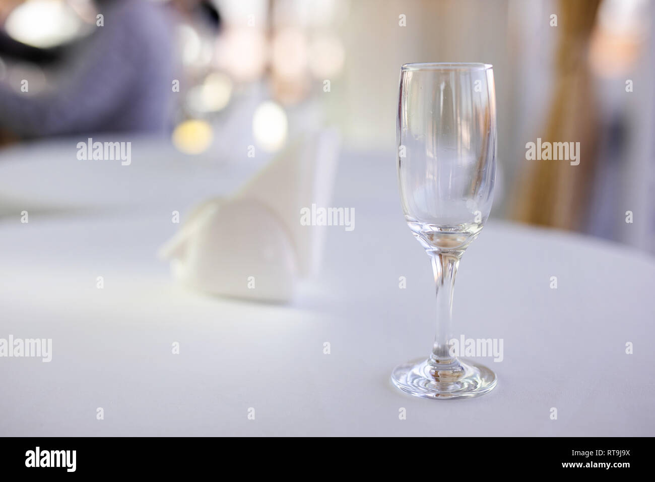 Natural light or daylight shot of modern restaurant table set for a lunch. Shallow focus on wine glass. - Stock Image