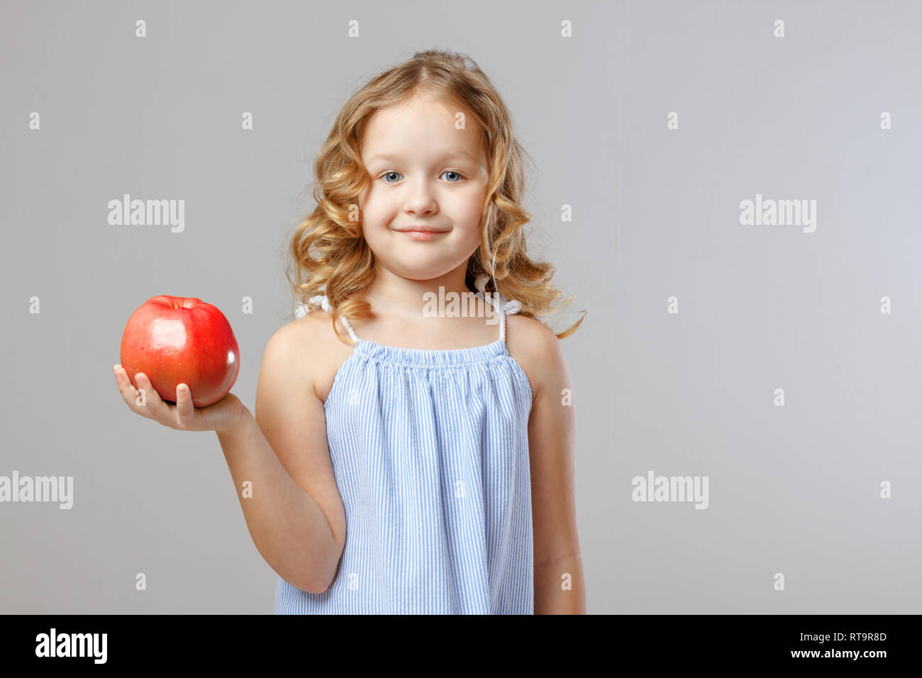 c880dc180c3 Portrait of an adorable little girl child holding in her hand a red apple.  Gray