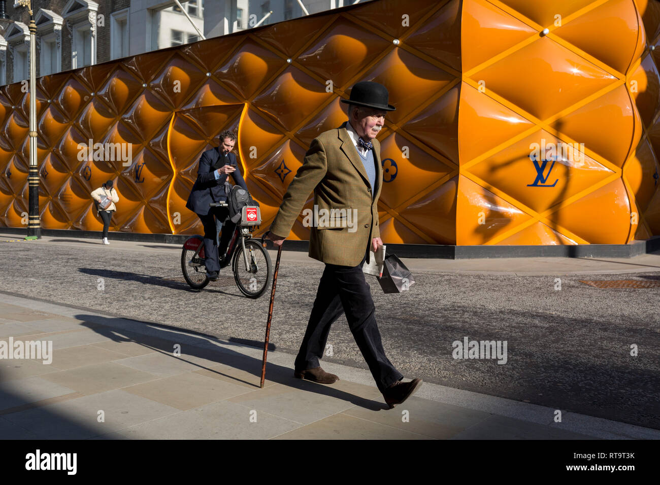 A classically-dressed English gentleman walks past the temporary renovation hoarding of luxury brand Louis Vuitton in New Bond Street, on 27th February 2019, in London, England. - Stock Image
