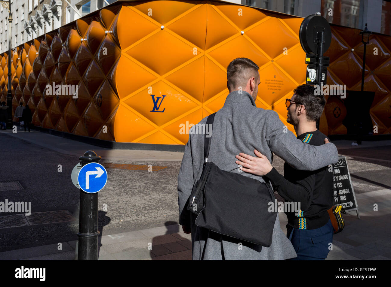 58bb65e90689 Friends greet each other opposite the temporary renovation hoarding of  luxury brand Louis Vuitton in New