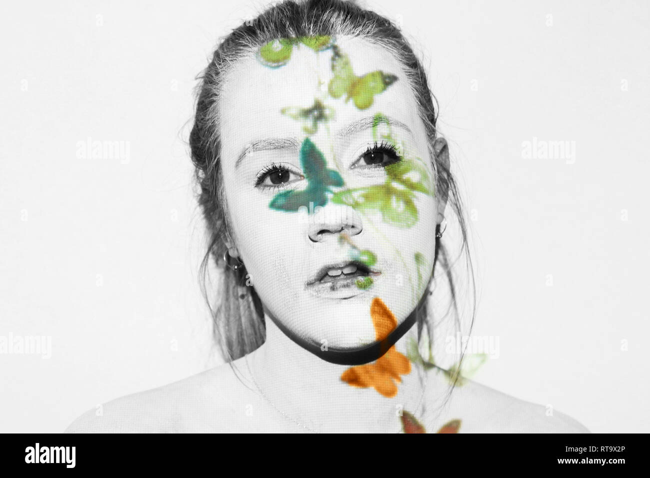 Woman covered in white paint has butterflies projected onto her. She looks emptily into the camera. - Stock Image