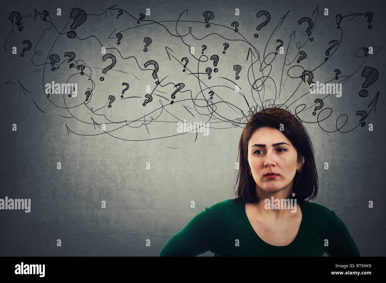 Serious and thoughtful young woman looking sad having a lot of questions like a mess coming out of. Anxiety stress and headache feeling. - Stock Image