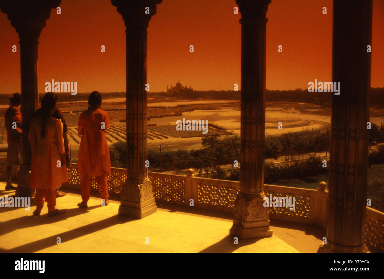 Indian tourists looking across Yamuna, Jumna, Jamuna, River, from Aurangzeb's apartment, prison at Taj Mahal from Red Fort Agra India - Stock Image