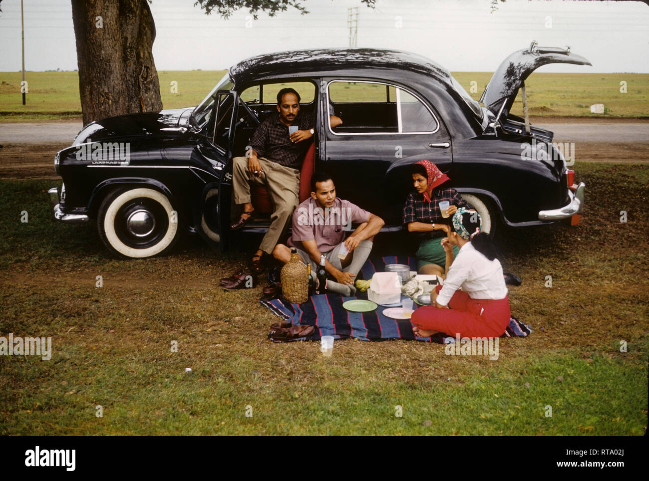 People having a picnic with Hindustan Landmaster car in India 1957 - Stock Image