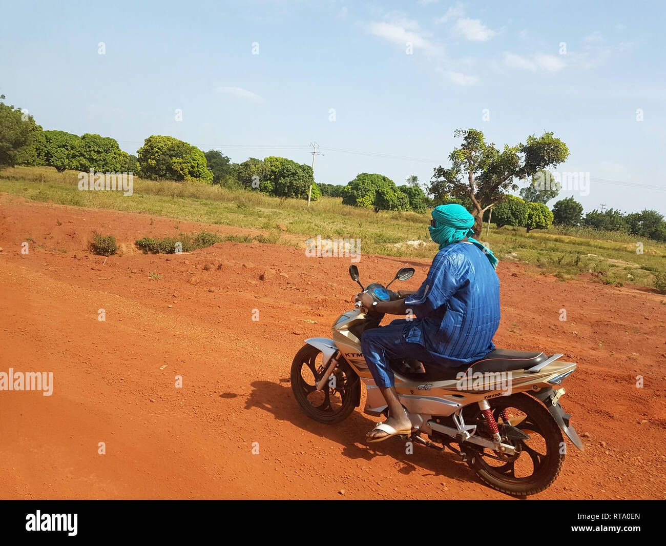 BAMAKO, MALI - DEC 19, 2016: African paysage with Touareg on his KTM bike driving fast ont the red african soil  Stock Photo