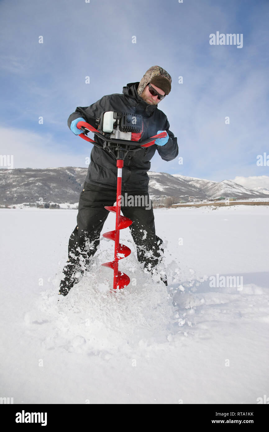 Adult ice fisherman drilling a hole in the ice at a lake using a power auger - Stock Image
