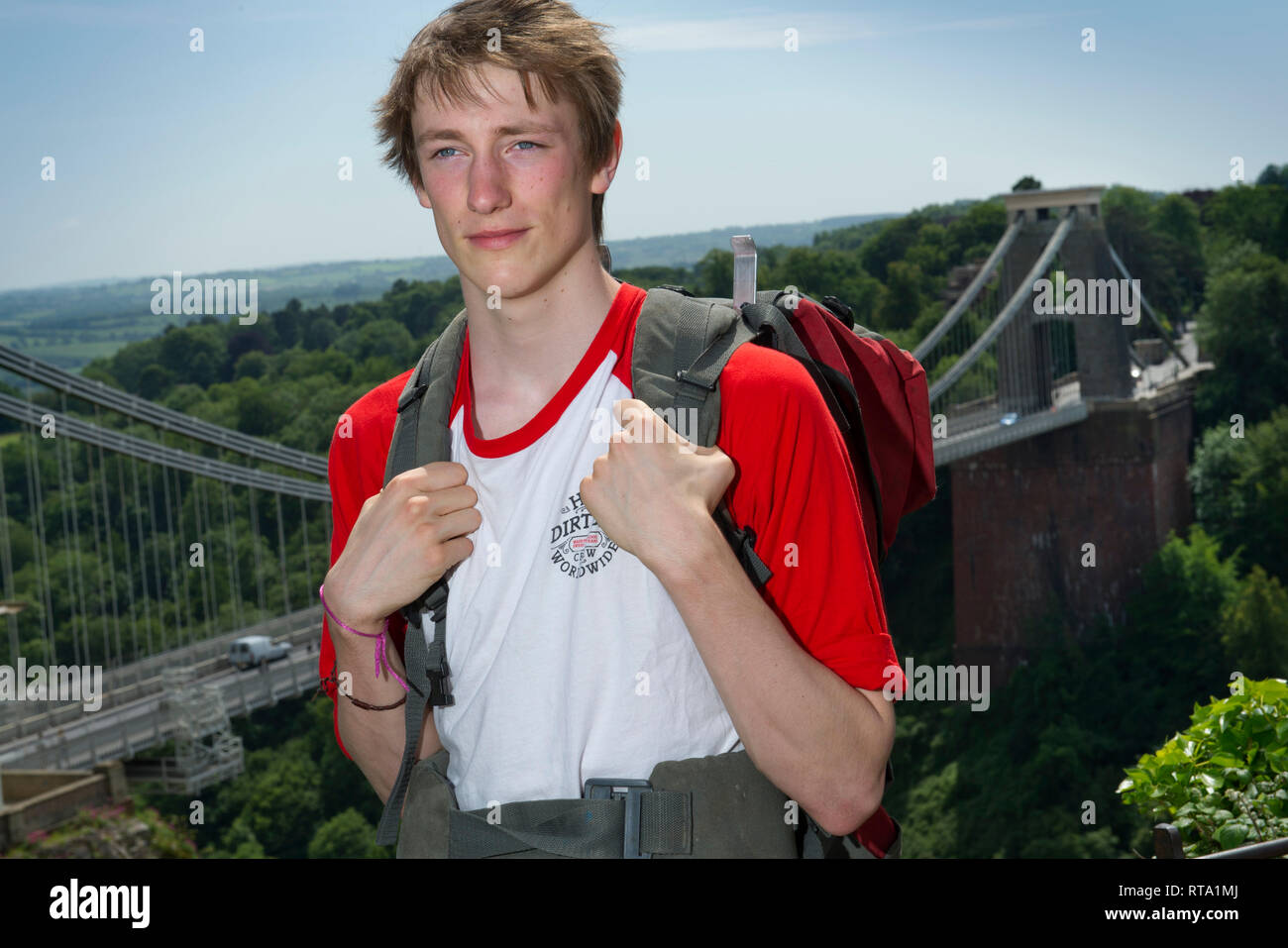 A travelling student, photographed with the Clifton Suspension Bridge, Bristol, UK - Stock Image