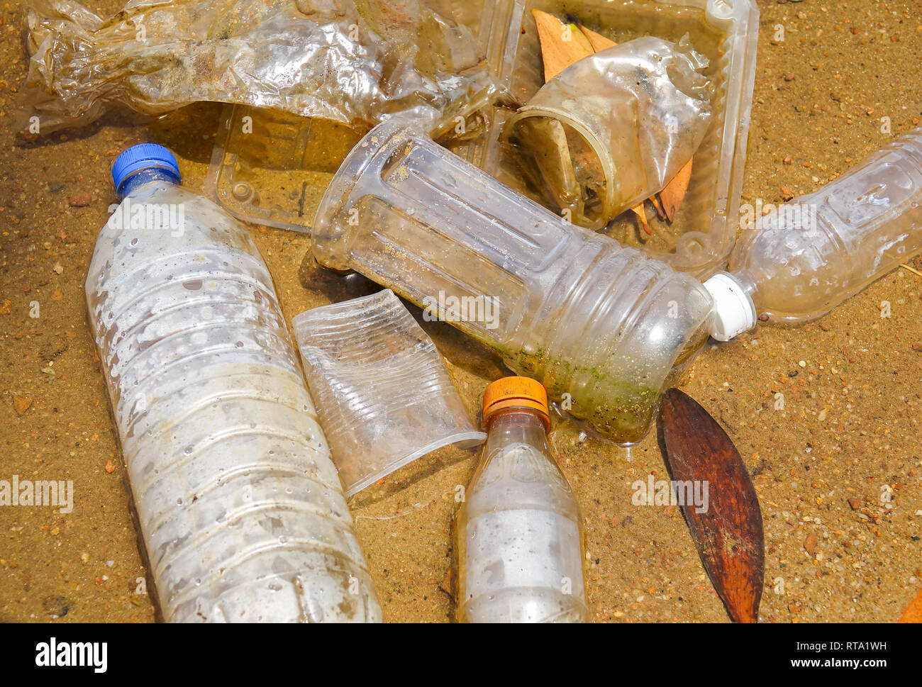 Bad enviromental habit of improper disposal of non-biodegradable PVC cups and bottles in a lake. Selective focus - Stock Image