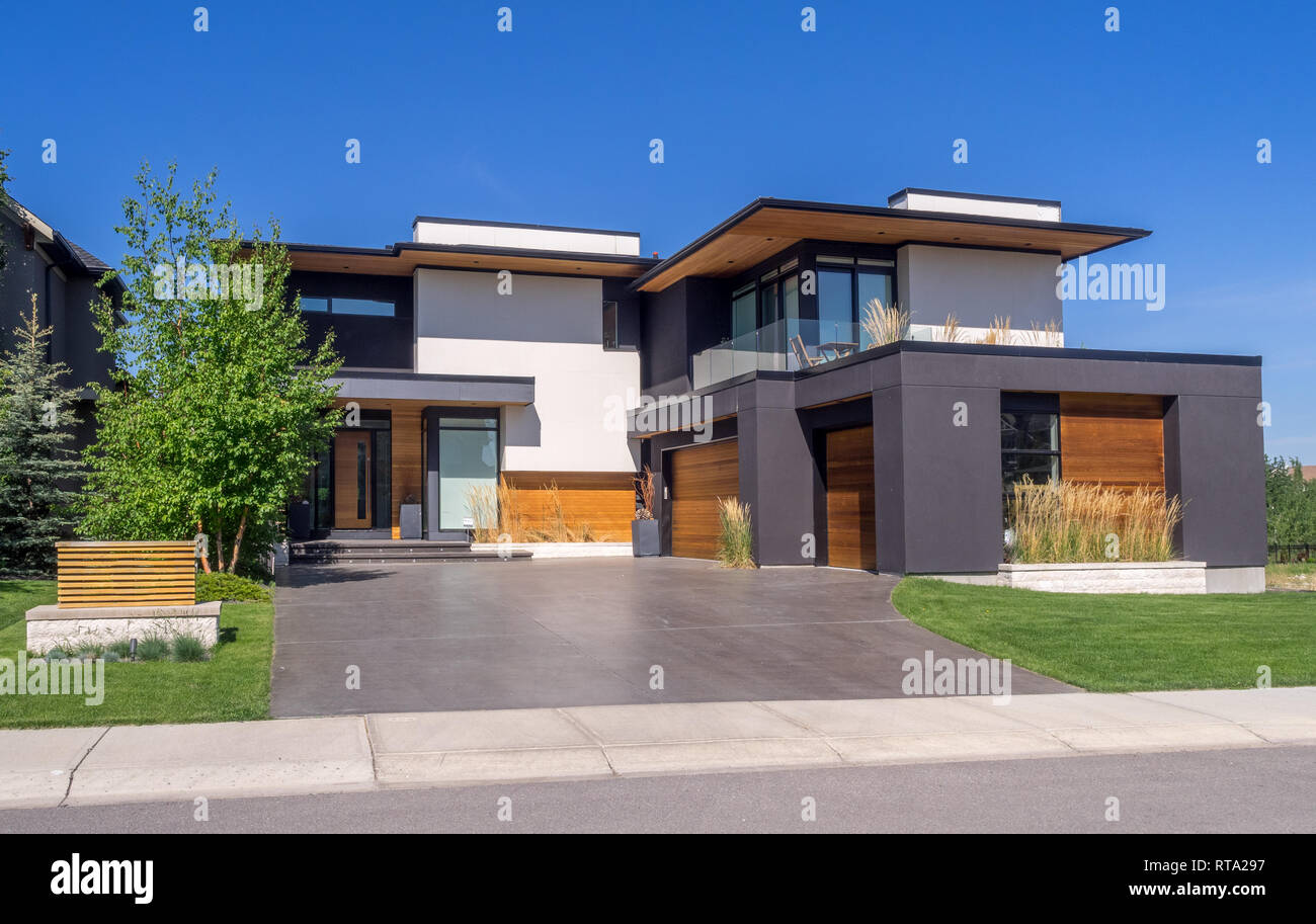 Luxury house at sunny day in Calgary, Canada. Taken from exterior on a sunny day. Each house has driveway and garage on the front of the house. Modern. Stock Photo