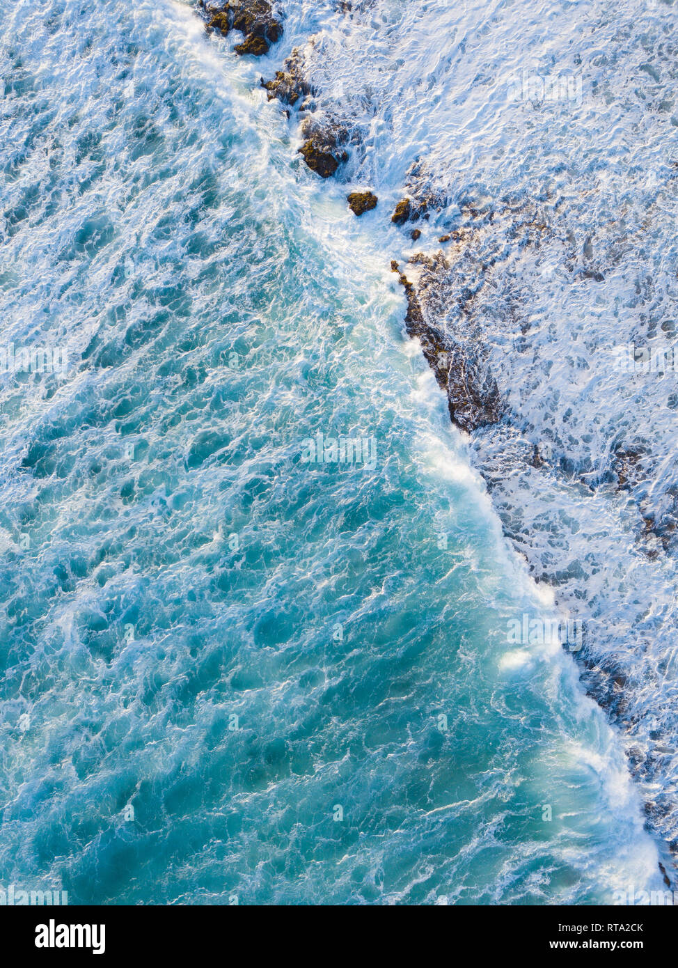 Aerial Drone shot showing the ocean and wave breaks against the reef - Stock Image