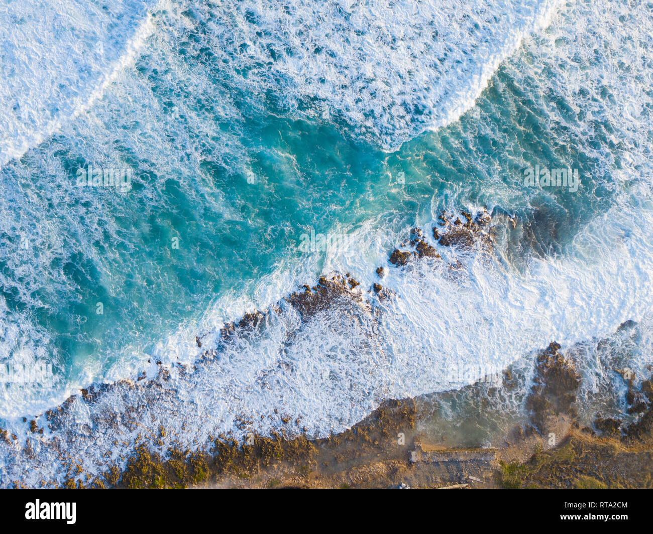Aerial Drone shot showing the ocean and wave breaks on the rocky coastline from above. - Stock Image