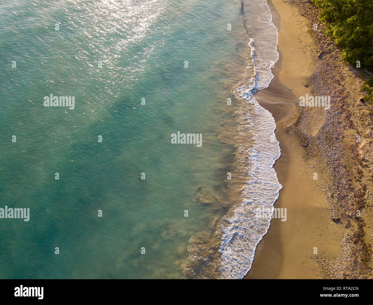 Aerial Drone shot showing the wave breaks on the  golden coloured sand beach - Stock Image