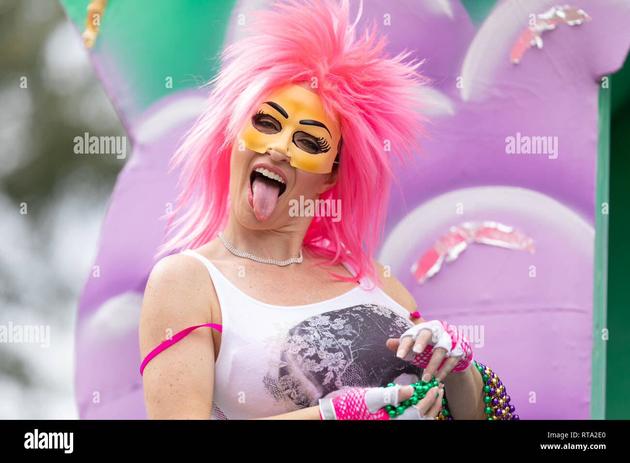 New Orleans, Louisiana, USA - February 23, 2019: Mardi Gras Parade, Woman wearing a pink wig and a face mask, showing her tongue and holding beads nec - Stock Image