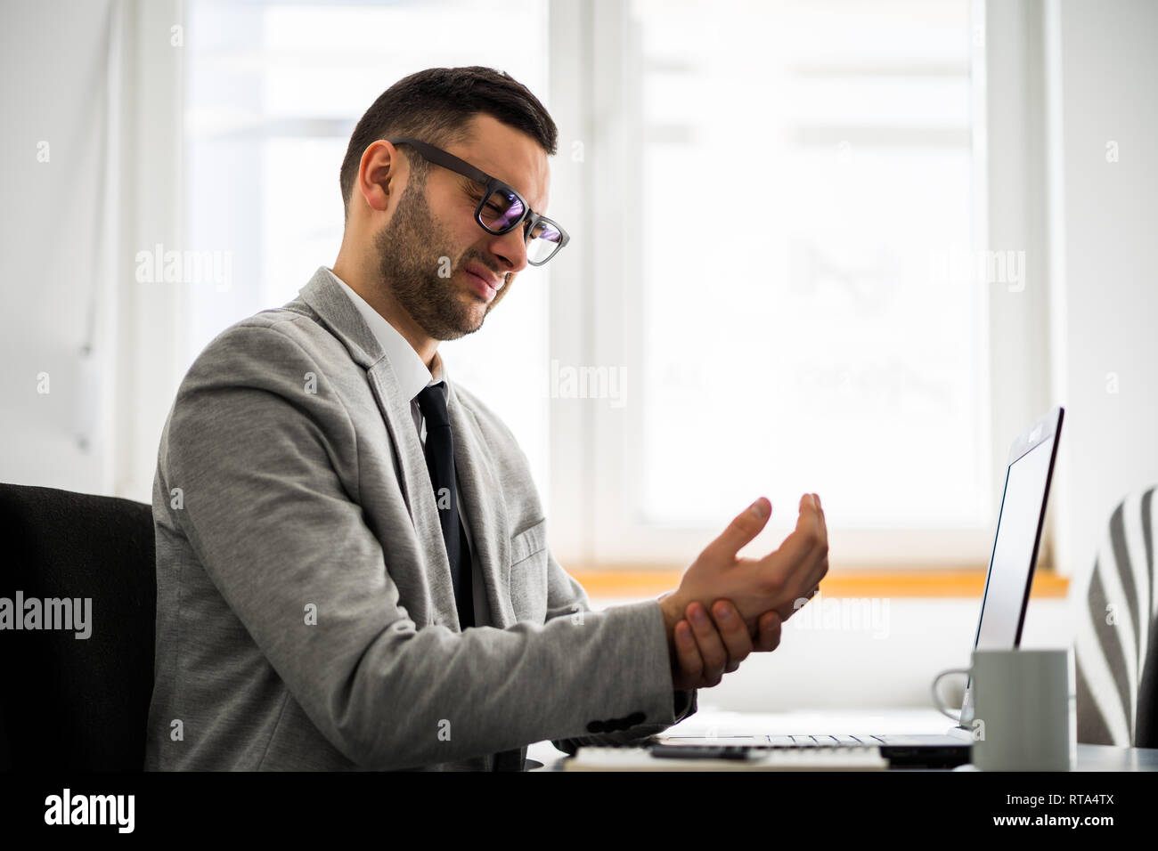 Young businessman is having pain in his arm. - Stock Image