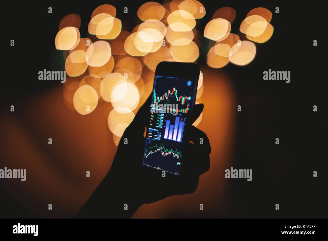 Silhouette of female hand holding smart phone in the dark with stock trading on display with light bokeh blurred background, Mobile business concept Stock Photo