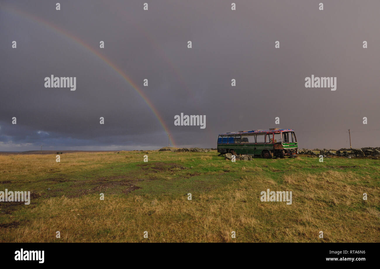 Stunning landscape with rainbow and old bus on the Isle of lewis, Scotland - Stock Image