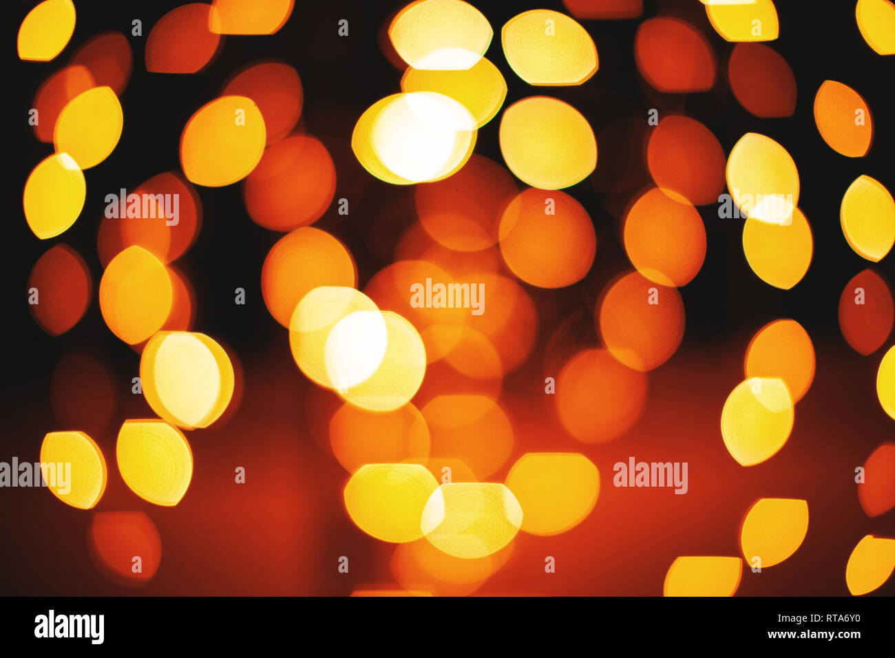 A group of circle and oval shape from red and yellow lights defocused abstract background, Lens aperture bokeh blurred effect Stock Photo