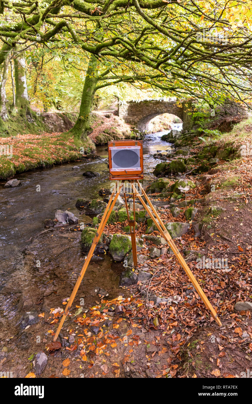 A traditional brass & mahogany large format 7 inch x 5 inch wooden camera on its original tripod being used to photograph Weir Water at Robbers Bridge - Stock Image