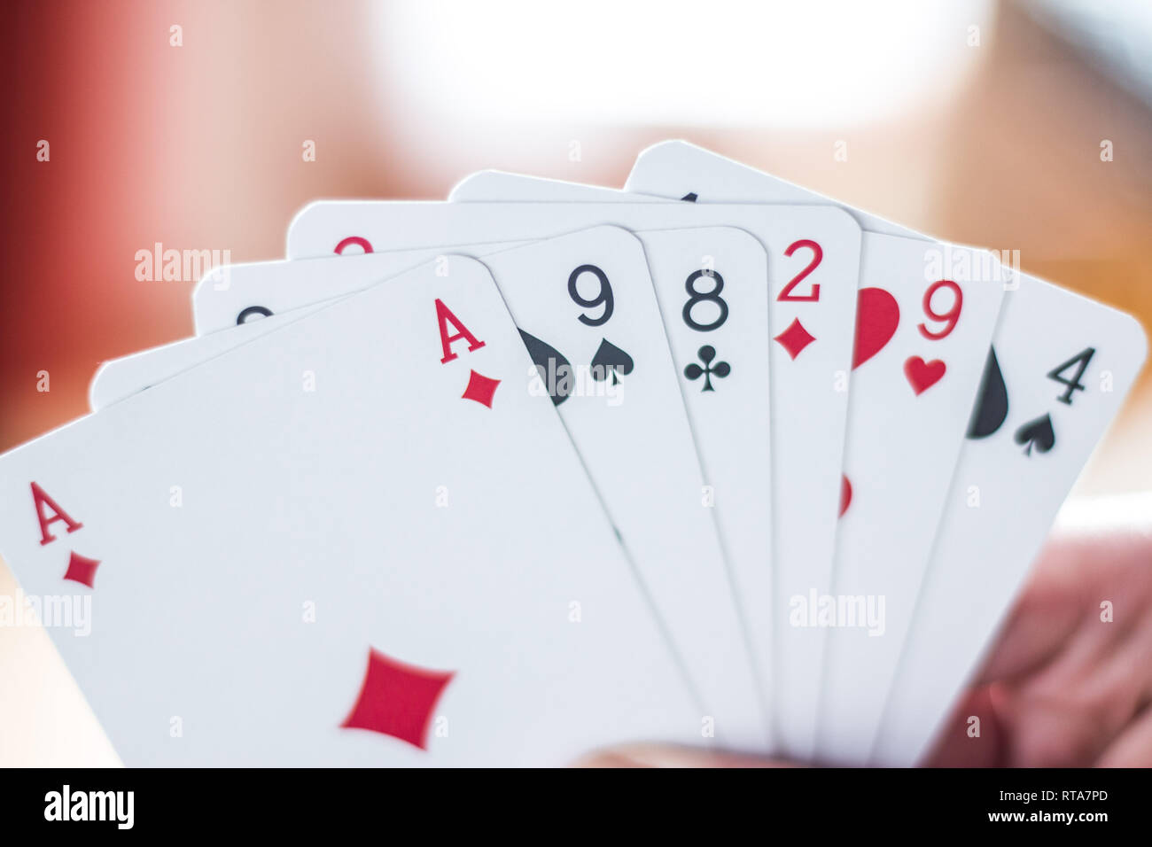 Young man is playing cards, cutout of his hands - Stock Image