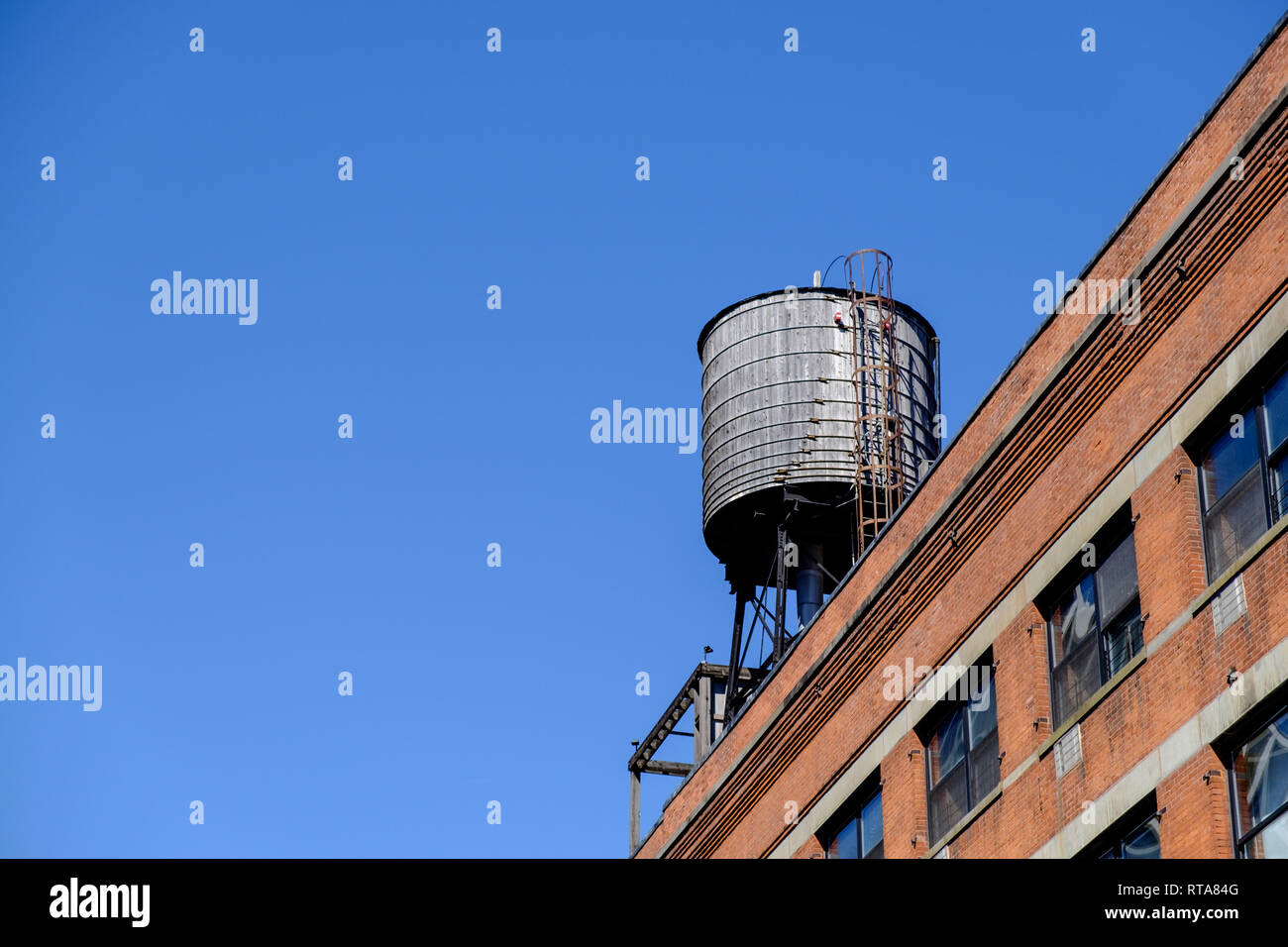 Old round water tower on the top of a building in Chelsea, New York City. Bright blue sky. March 18, 2018 - Stock Image