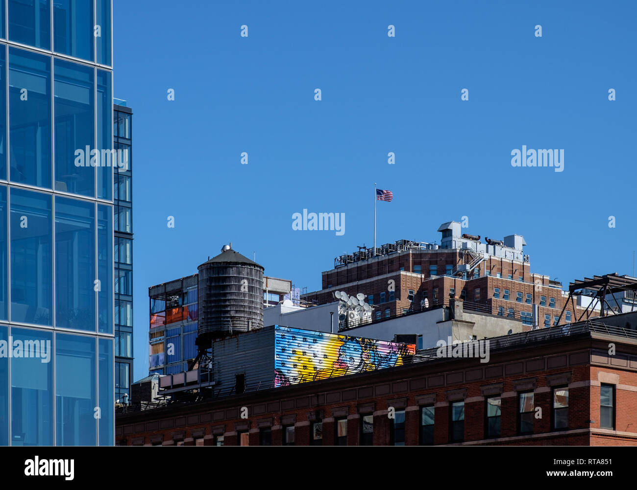 Rooftops with American flag, old round water tank, & painted graffiti in West Side, Manhattan, New York City, Mar 18, 2018. - Stock Image