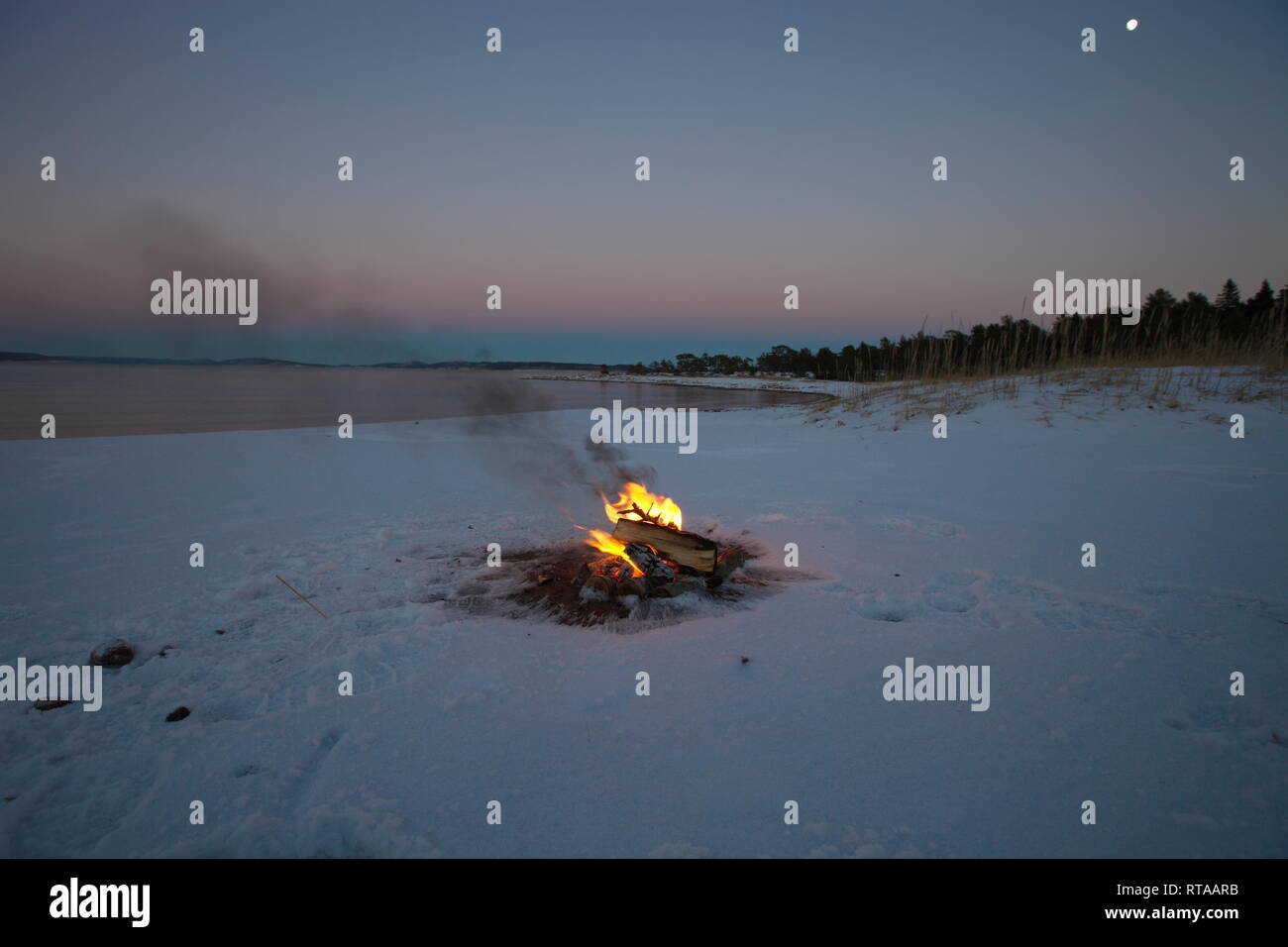 A camp fire is burning at the shore of a bay of the Baltic Sea. It's sunset on a winter day and the beach is covered in snow. Stock Photo