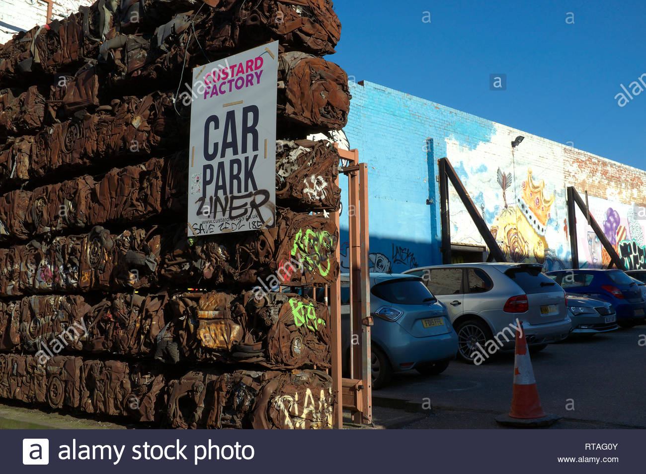 Car parking for the Custard Factory - creative use of baled crushed cars and wall murals in the Digbeth area of central Birmingham, West Midlands, UK. Stock Photo