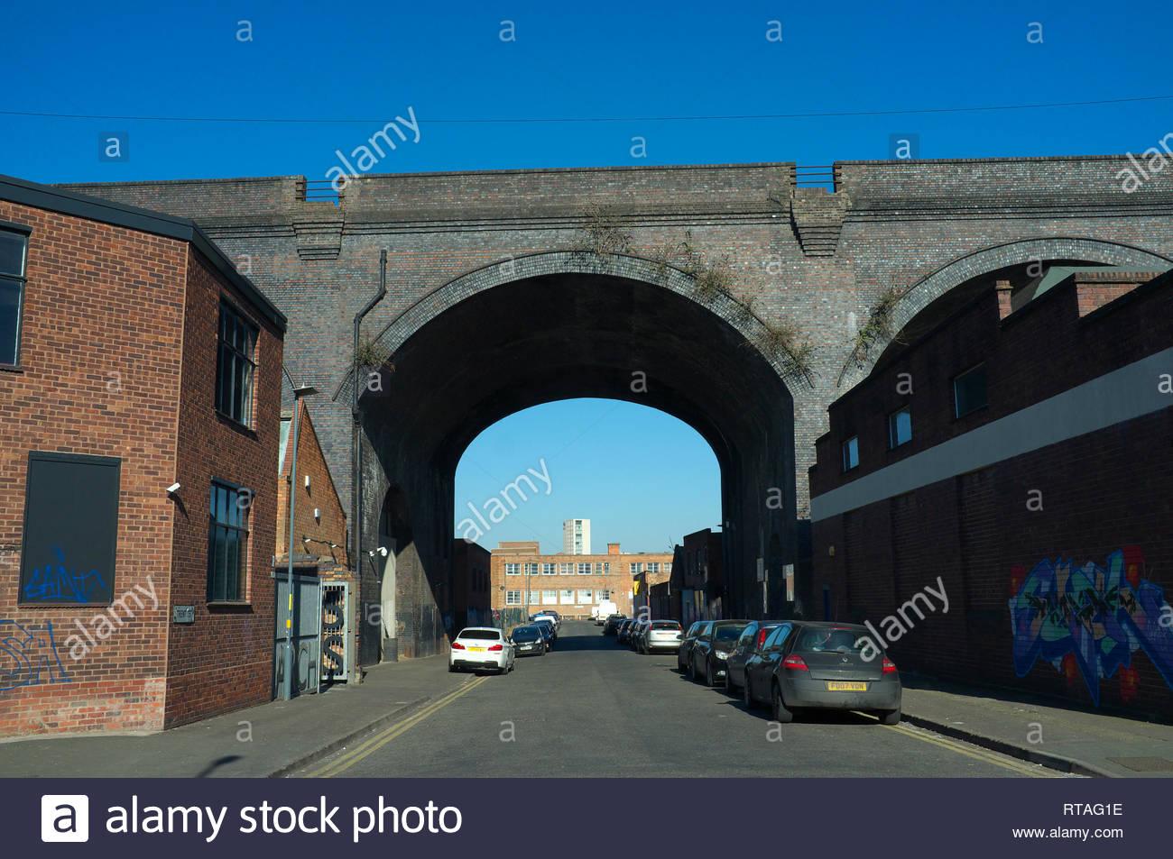 Railway viaduct passes over industrial premises, in Trent Street, central Birmingham, West Midlands, UK. Stock Photo