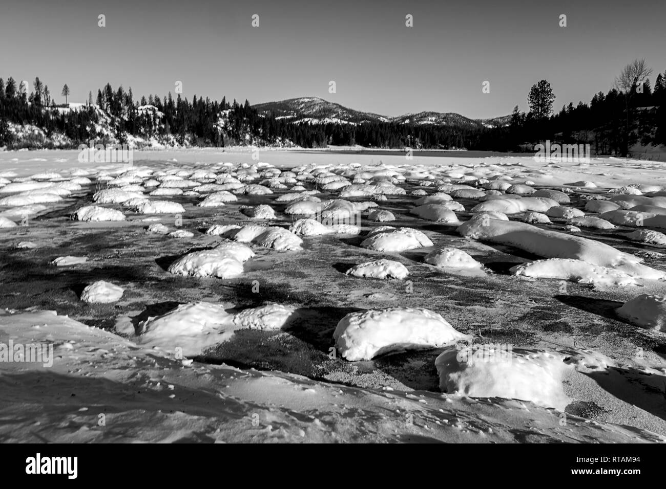 A black & white landscape photo of a cold winter scenic on a clear day in Hauser, Idaho. - Stock Image