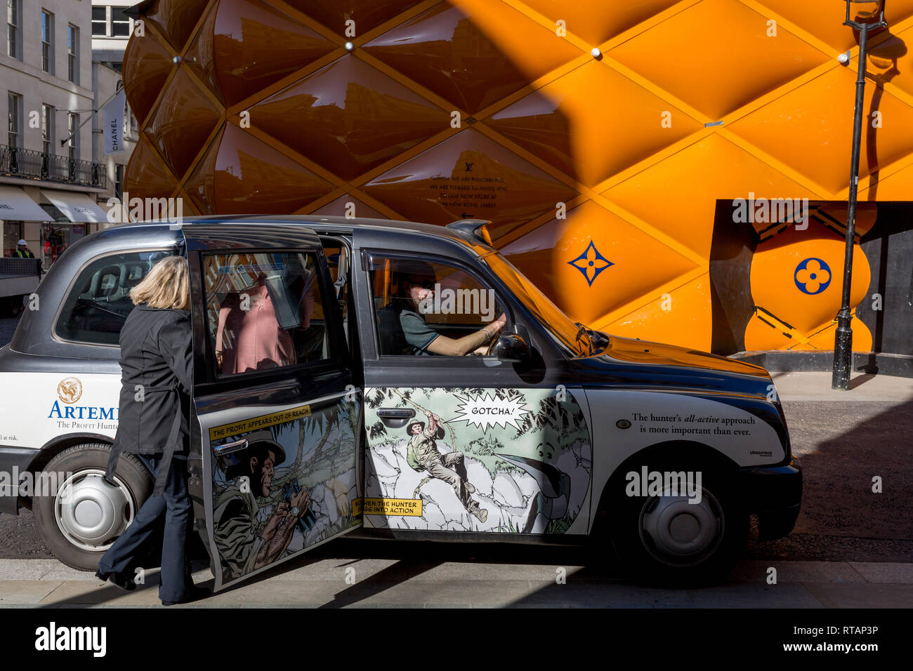 A black cab picks up fares opposite the temporary renovation hoarding of luxury brand Louis Vuitton in New Bond Street, on 25th February 2019, in London, England. - Stock Image