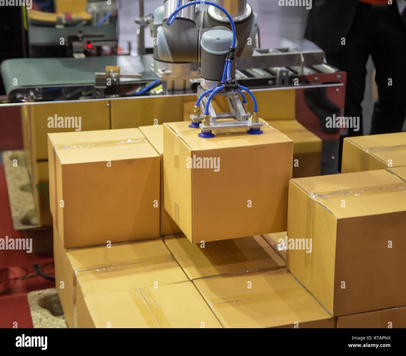 The universal robot lifting carton to production line - Stock Image