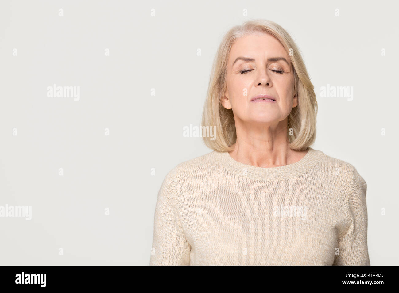 Calm mid aged woman breathing fresh air isolated on background - Stock Image