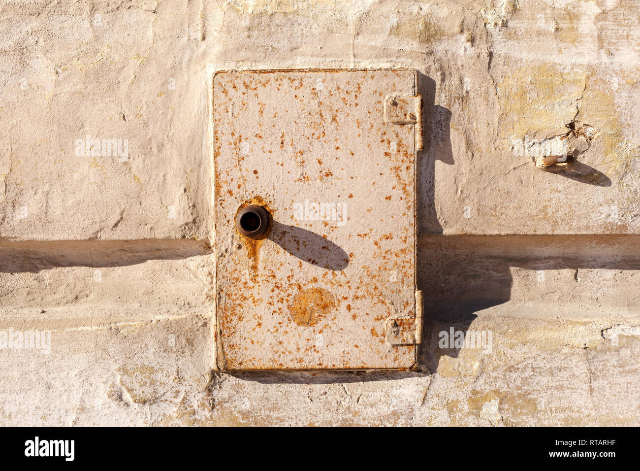 Rusty metal door of the electric box. Old abandoned electrical junction box on the wall of an old house. Stock Photo