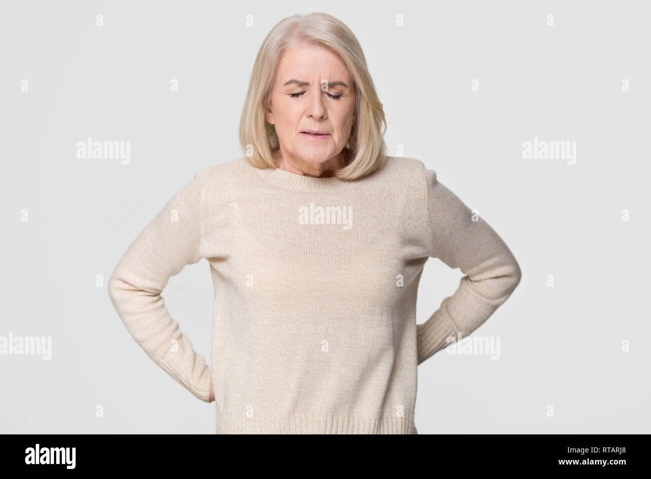 Upset old woman touching back feeling pain isolated on background - Stock Image
