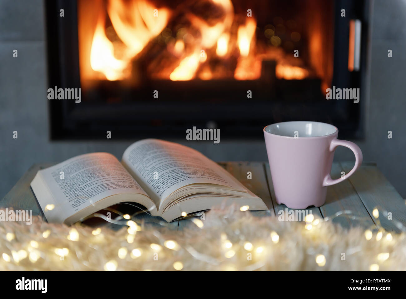 Book and cup of tea near burning fireplace. Hygge concept - Stock Image
