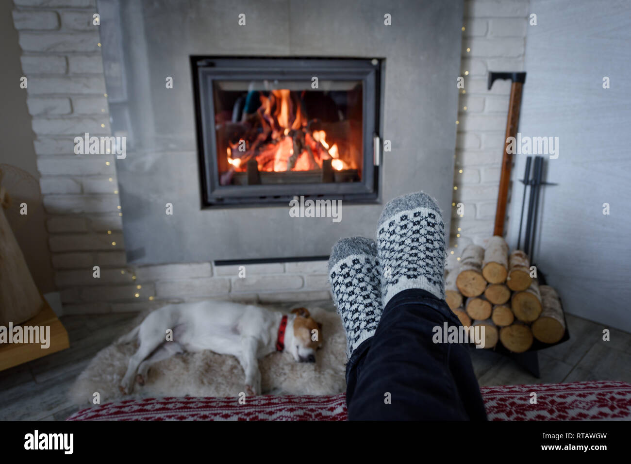 Burning fireplace and man feet in wool socks on foreground. Hygge concept - Stock Image