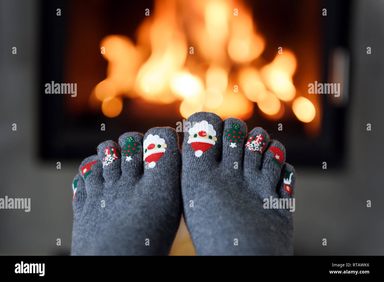 Burning fireplace and girl feet in funny wool socks on foreground. Hygge concept - Stock Image
