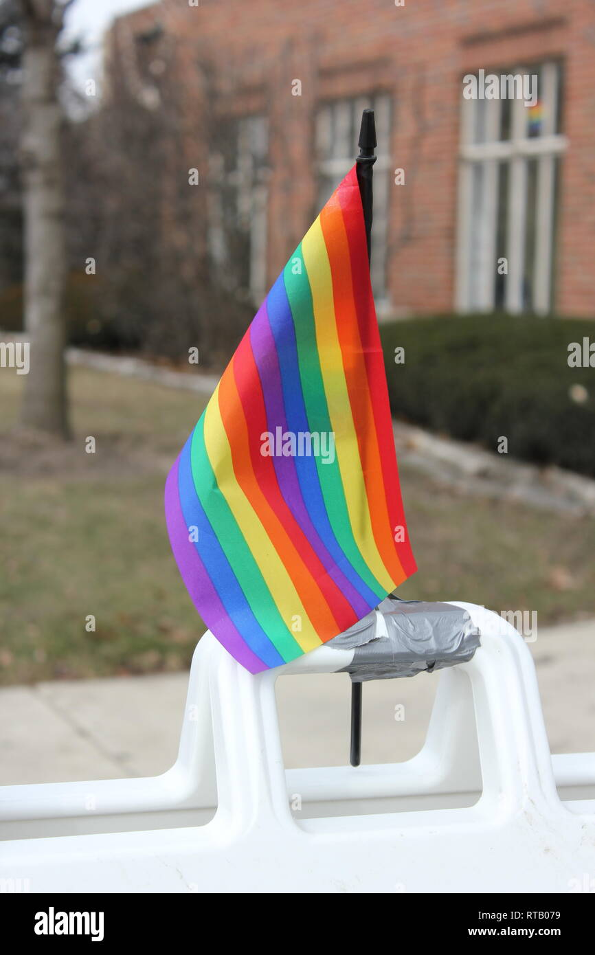 A perched rainbow flag as an expressive announcement of acceptance of gay and lgbtq people. - Stock Image