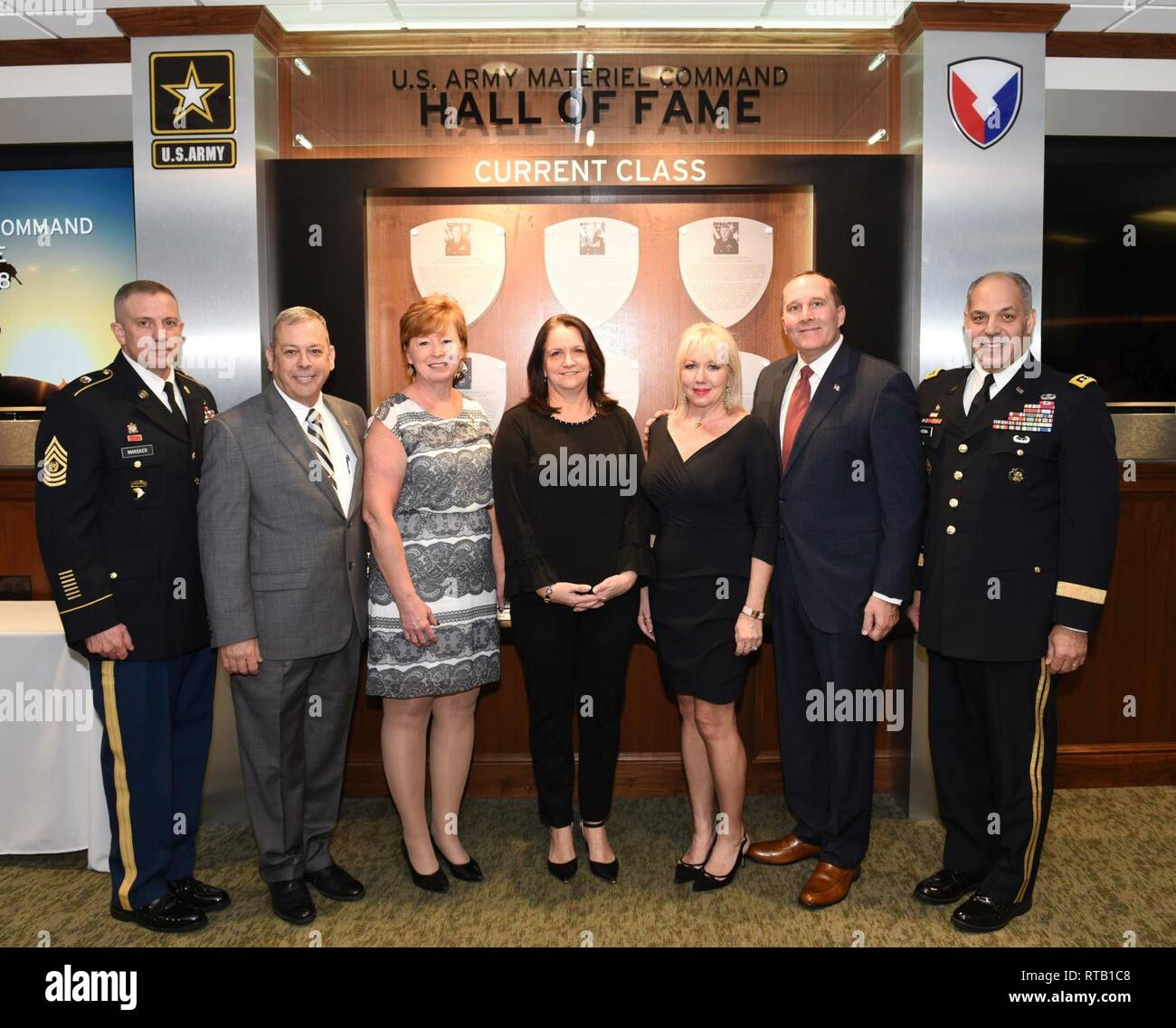 Retired Command Sergeants Major Daniel Elder, second from left, and Ronald Riling, second from right, are honored at an Army Materiel Command Hall of Fame Induction Ceremony Feb. 5 at AMC headquarters, Redstone Arsenal, Ala. With them are, from left, AMC Command Sgt. Maj. Rodger Mansker, Gloria Elder, Susan Perna, Melinda Riling and AMC commander Gen. Gus Perna, who hosted the ceremony. - Stock Image