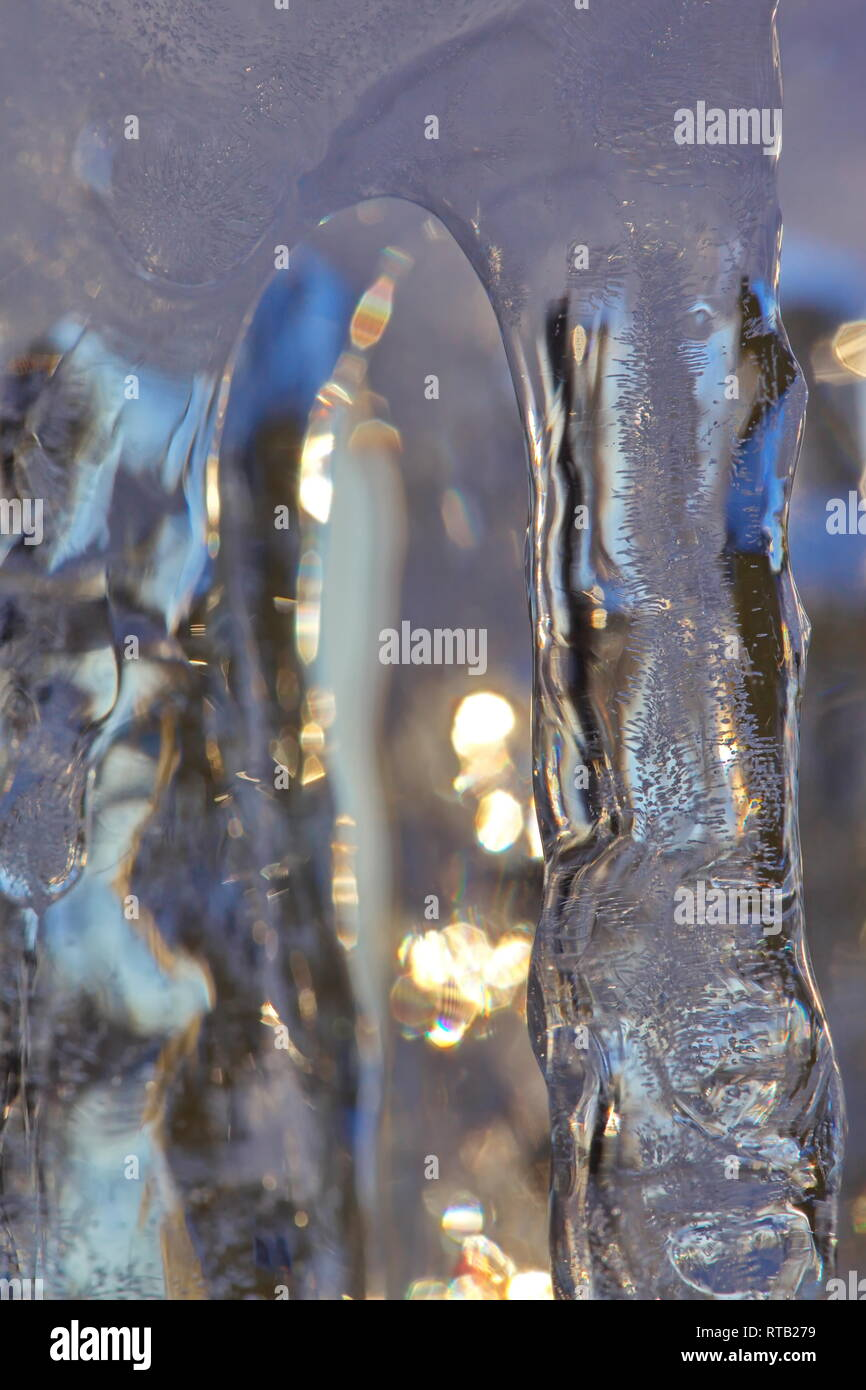 Close up of a row of icicles glittering in the light of the golden winter sun. Stock Photo
