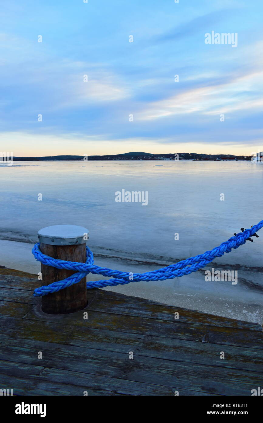 Close up of a blue rope mooring a ship in an ice covered harbor bay. Stock Photo