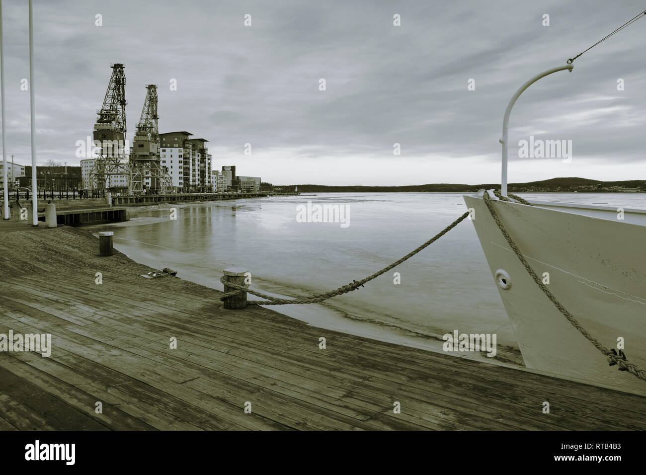 A ship lies moored in an ice covered harbor bay. Monochrome photograph,tones sepia and blue. - Stock Image